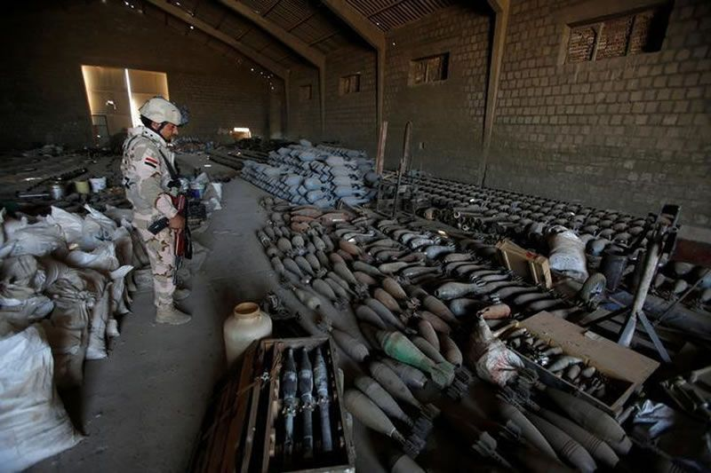 A member of Iraqi army stands near weapons that belonged to Islamic State militants, at an Iraqi army base in Camp Tariq near Falluja, Iraq, September 4, 2016. REUTERS/Khalid al Mousily