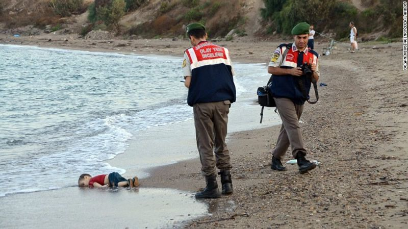 """Authorities stand near Alan's lifeless body on September 2, 2015. This photo went viral around the world, often with a Turkish hashtag that means """"Flotsam of Humanity."""""""