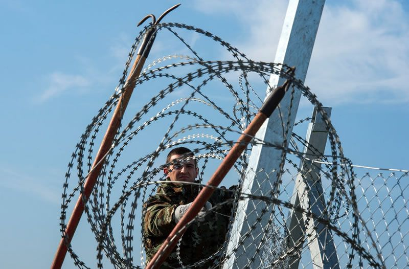 A Macedonian soldier placing barbed wire on a new fence along the border with Greece near Gevgelija, Macedonia. Georgi Licovski/European Pressphoto Agency