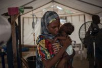 A woman holds her young baby during a check-up at the In-Patient Therapeutic Feeding Centre in the Gwangwe district of Maiduguri, the capital of Borno State, northeastern Nigeria, on September 17, 2016. Aid agencies have long warned about the risk of food shortages in northeast Nigeria because of the conflict, which has killed at least 20,000 since 2009 and left more than 2.6 million homeless. STEFAN HEUNISSTEFAN HEUNIS/AGENCE FRANCE-PRESSE via Getty Images