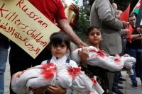 "Children hold dolls symbolizing dead babies during in a sit-in in solidarity with the people of Aleppo and against Russia's support of the Syrian regime, in front of the Russian embassy in Amman, Jordan, May 3, 2016. The placard reads, ""Russian are baby killers"". REUTERS/Muhammad Hamed"