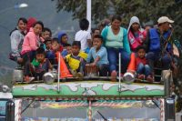 Colombian indigenous people of the Nasa ethnic group are transported on the roof of a local transport vehicle in Toribio, Colombia, on Oct. 3. (LUIS ROBAYO/Agence France-Presse via Getty Images)