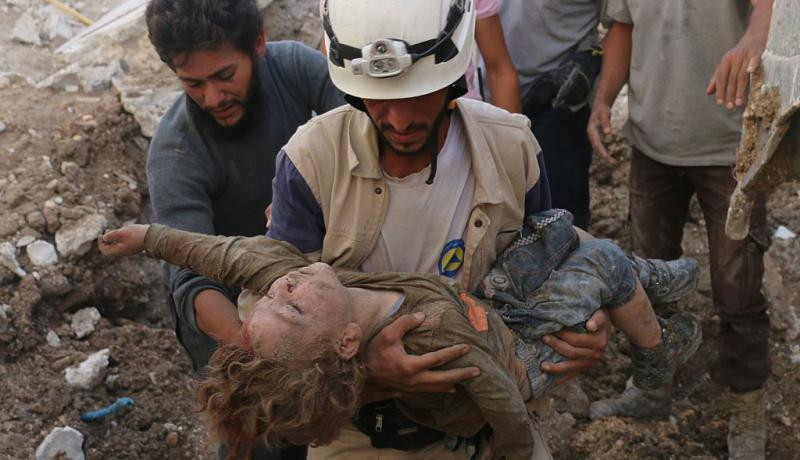 A Syrian civil defence volunteer, known as the White Helmets, holds a child after he was pulled from the rubble following an air strike on Aleppo. Photo by AMEER ALHALBI/AFP/Getty Images - See more at: https://www.chathamhouse.org/expert/comment/syria-destruction-civil-society-means-dictatorship-extremism-and-further-displacement#sthash.TtxYrYjW.dpuf