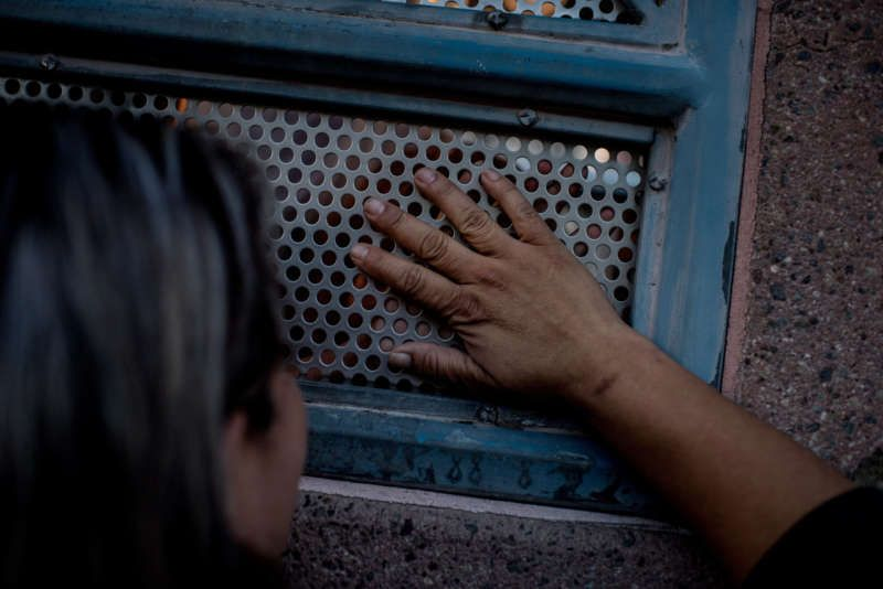 Gaby Jiminez speaks with her sister, Trinidad, through the border barrier. Tomás Munita for The New York Times