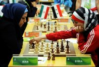 Fatemah al-Jeldah, right, of Syria making a move as she plays against Atous Pourkashiyan of Iran in tournament play. Credit Goh Chai Hin/Agence France-Presse — Getty Images