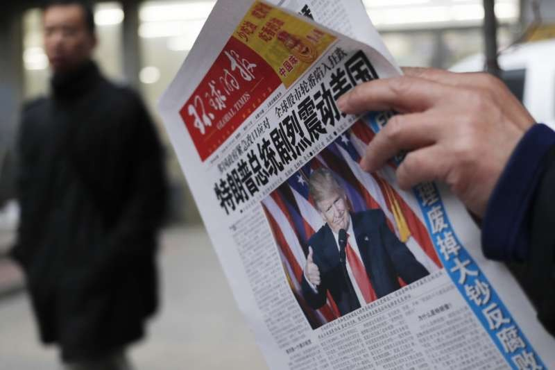 A man reads a newspaper in Beijing. (Andy Wong/Associated Press)