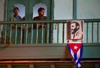 Dos residentes miran a través de las ventanas de su casa en La Habana, Cuba, el sábado 26 de noviembre, un día después de la muerte de Fidel Castro. Credit Ramon Espinosa/Associated Press