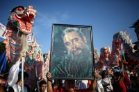 People carry a picture of Fidel Castro during a May Day rally in Havana on May 1, 2016. (Alexandre Meneghini/Reuters)
