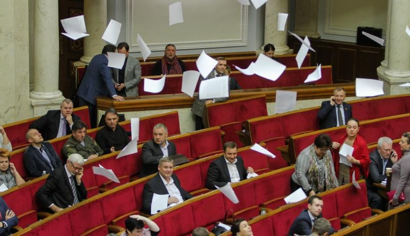 After Ukrainian officials declared millions of dollars in cash and other assets, activists throw leaflets during a Verkhovna Rada (parliament) session in Kyiv, 1 November 2016. Photo via Getty Images.