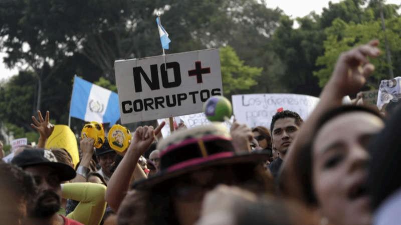 """Los manifestantes gritan consignas y sostienen un cartel que dice """"No más corruptos"""", durante una manifestación contra un escándalo de corrupción política en el centro de la ciudad de Guatemala, el 25 de abril de 2015. REUTERS / Jorge Dan Lopez"""