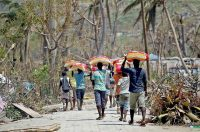 After Hurricane Matthew, young men carry bags of rice they got from a food distribution center near Port Salut, Haiti. PATRICK FARRELL