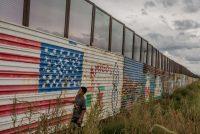 Yair Sanchez, de 12 años, examina los dibujos en el muro fronterizo en su barrio en Naco, México. Credit Tomas Munita para The New York Times