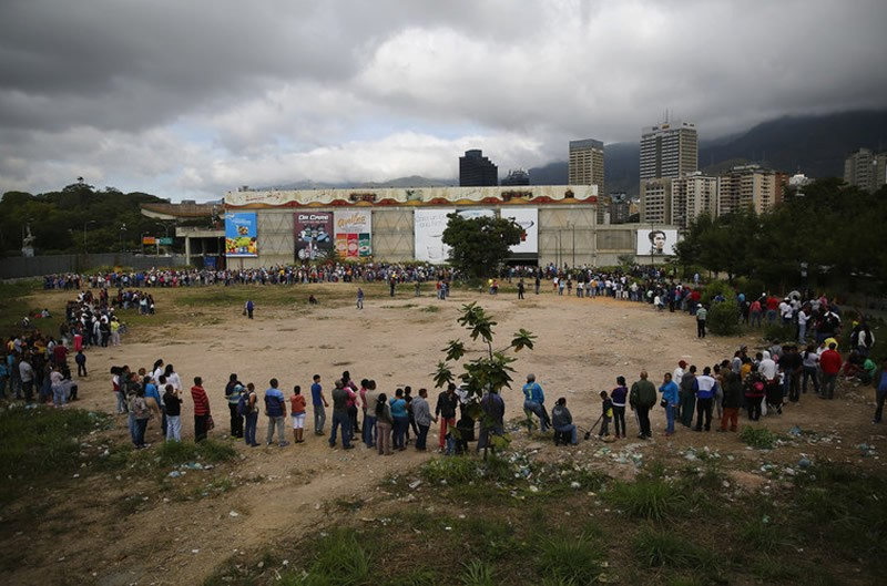 People queuing outside a state-run supermarket store in Caracas to buy basic necessities. Jorge Silva/Reuters