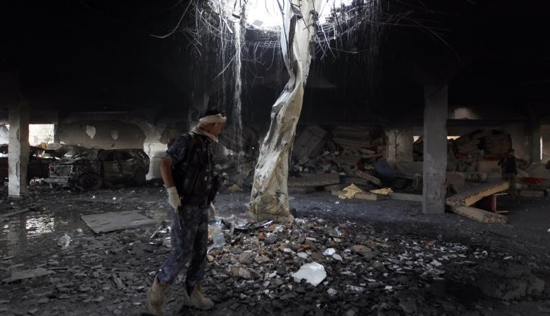 A Yemeni inspects the rubble of a destroyed funeral hall building. Photo by Getty Images.