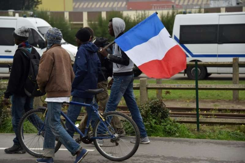 """Migrants holding a French flag walk in the """"Jungle"""" migrant camp in Calais, France, on Oct. 24. (Philippe Huguen/Agence France-Presse via Getty Images)"""