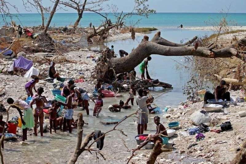 Women left destitute after Hurricane Matthew bathe and clean clothes in a river cutting through Roche-a-Bateau. Patrick Farrell Miami Herald