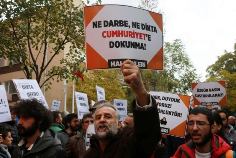 """Participants hold placards reading """"Do not touch Cumhuriyet"""" outside the headquarters of Turkish newspaper Cumhuriyet in Ankara on Oct. 31, during a protest against the detention of the newspaper's editor-in-chief and a dozen journalists and executives. (Adem Altanadem Altan/Agence France-Presse via Getty Images)"""