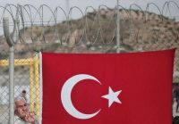 A migrant man stands behind a fence, decorated with a Turkish flag at the Nizip refugee camp in Gaziantep province, southeastern Turkey on April 23. (Lefteris Pitarakis/Associated Press)