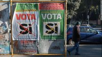 """A man walks past posters calling for a """"Yes"""" vote in Italy's constitutional referendum."""