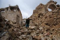 A Syrian man makes his way through the rubble of destroyed buildings as he heads to his house in Aleppo's Dahret Awad neighborhood on Dec. 17 after pro-government forces retook the area from rebel fighters. (Youssef Karwashan/AFP/Getty Images)