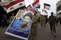 Supporters of the Syrian regime carrying a poster of Bashar al-Assad and Sayyed Hassan Nasrallah, the leader of Iran-backed Hezbollah, Ansar village, Lebanon, March 2, 2016. Ali Hashisho/Reuters