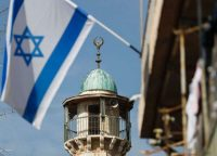 An Israeli flag waves in front of the minaret of a mosque in the Arab quarter of Jerusalem's Old City on Nov. 14. (Thomas Coex/AFP via Getty Images)