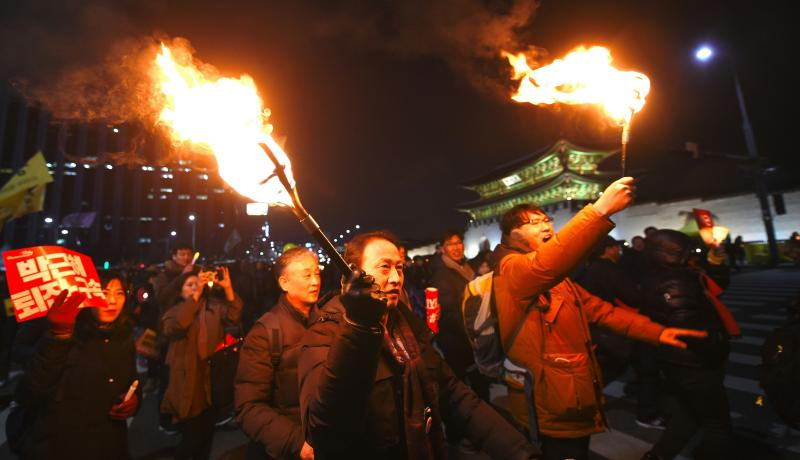 South Korean protesters hold torches during a rally against the president in central Seoul. Photo by Getty Images.