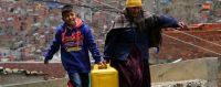 Une femme et un enfant transportent un bidon d'eau distribué aux habitants des quartiers de La Paz touchés par la sécheresse, 22 novembre 2016. © MARTIN ALIPAZ / EPA