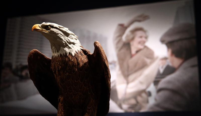 An American bald eagle model gifted to Margaret Thatcher by Ronald Reagan in front of a photograph of Thatcher.