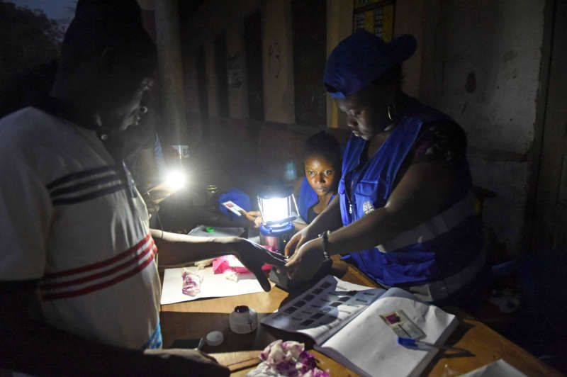 Ghanaian election officials use a lantern and a smartphone torchlight to assist people voting late at a polling station in Tamale this month. Pius Utomi Ekpei/Agence France-Presse — Getty Images