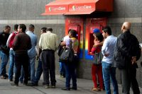 People line up to withdraw money from an ATM in Caracas on Thursday. (Federico Parra/Agence France-Presse/Getty Images)