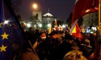 Demonstrators hold Polish and E.U. flags during a protest outside the parliament building in Warsaw on Dec. 17. (Kacper Pempel/Reuters)