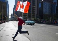 A man with a Canadian flag runs in front of parade marshal William Shatner during the Calgary Stampede parade in Calgary, Alberta, in 2014. (Todd Korol/Reuters)