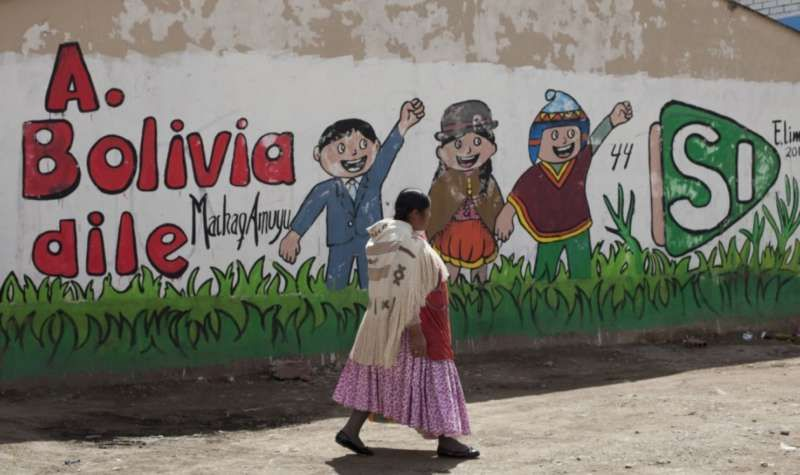 """An Aymara woman walks past a mural that reads in Spanish """"Tell Bolivia Yes,"""" in favor of President Evo Morales, in El Alto, Bolivia, in February, days before a referendum on whether to amend the constitution so that Morales could run in 2019 for a fourth consecutive term. (Juan Karita/Associated Press)"""