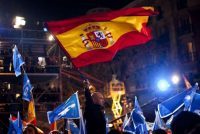 Supporters of the conservative Popular Party wave party and Spanish flags next to their party headquarters in Madrid. (Emilio Morenatti/Associated Press)