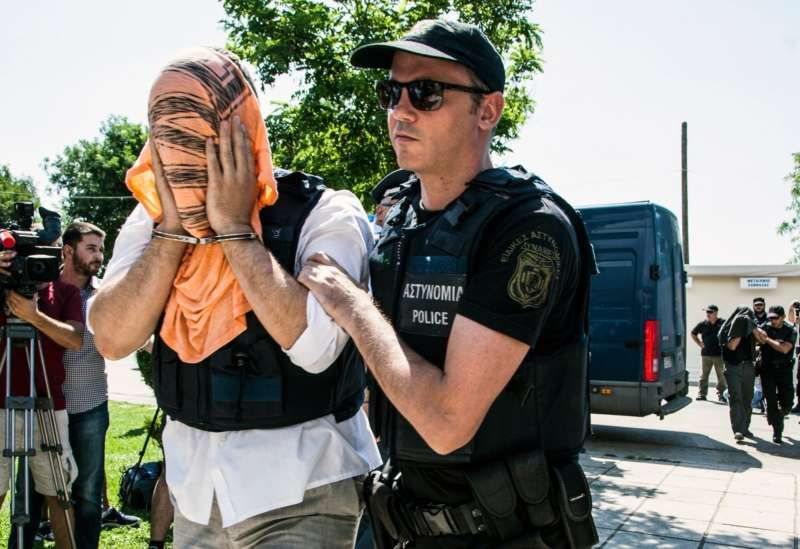 A Turkish military officer being transferred to court in northern Greece in July. Antonis Pasvantis/Associated Press