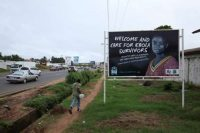 A man walks past a billboard to educate Liberians about the treatment of Ebola in Monrovia on July 10, 2015. (Ahmed Jallanzo/European Pressphoto Agency)