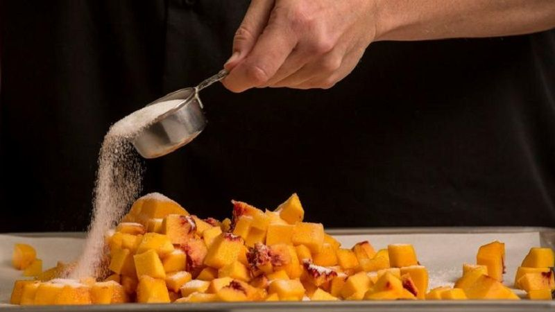 Diced peaches are coated with sugar for a frozen yogurt recipe being tried out in the Los Angeles Times test kitchen in 2016. (Los Angeles Times)