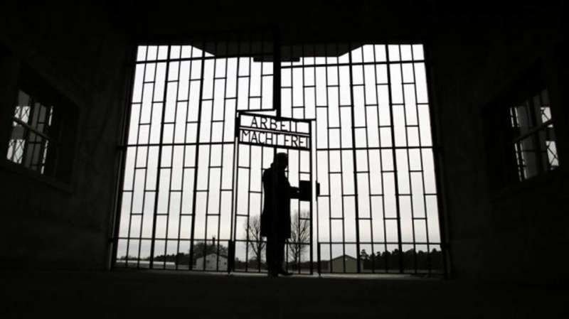 A man enters the Sachsenhausen death camp through the gate on International Holocaust Remembrance Day 2016. Markus Schreiber AP