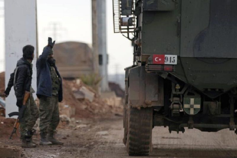Free Syrian Army fighters gesture as Turkish military vehicles drive in the Syrian rebel-held town of al-Rai while heading towards the northern Syrian town of al-Bab, Syria January 9, 2017. REUTERS/Khalil Ashawi