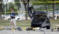 A man stands next to assailants' car in Garland, Texas, USA, used in a lone wolf attack carried out by two gunmen in 2015