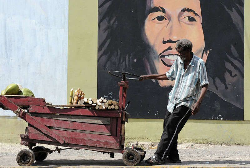 A vendor pulling his cart in front of a mural of Bob Marley, Kingston, Jamaica, February 8, 2009. Jewel Samad/AFP/Getty Images.