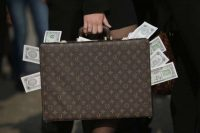 An activist seeking more transparency in government clutches a suitcase stuffed with fake money on April 13, 2016, in Berlin. (Sean Gallup/Getty Images)