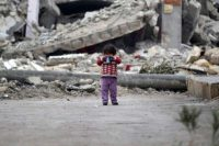 A girl plays amid the rubble of destroyed buildings in Rai town in northern Aleppo province. (Khalil Ashawi/Reuters)