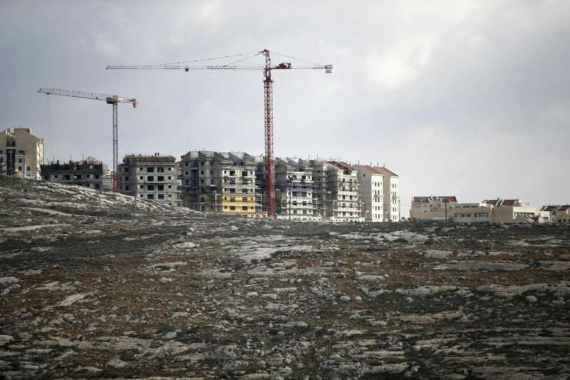 A picture taken on Jan. 3, 2017 shows Israeli construction cranes and excavators at a building site of new housing units in the Jewish settlement of Kochav Ya'akov near the West Bank city of Ramallah. (AFP PHOTO/AHMAD GHARABLI)