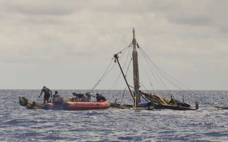 A Philippine Coast Guard boat, left, approaches a sinking Filipino fishing boat near Zamboanga City, southern Philippines. Government officials reported several Filipino fishermen on the boat were killed by a group of suspected pirates. (Philippine Coast Guard via AP)