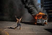 A student near a burning bus during clashes with the police after a protest over tuition fees in Johannesburg in 2016. Mujahid Safodien/Agence France-Presse — Getty Images