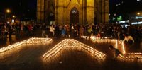 People light candles during a peace vigil in Bogota May 22, 2014. Colombians vote on Sunday in a tightly fought presidential election that has seen the top two candidates tainted by scandal as they wrestle over the pivotal issue of how to end a five-decade insurgency by Marxist FARC rebels. REUTERS/ John Vizcaino