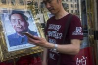A man on a mobile phone passes a portrait of Mao Zedong in Beijing on May 20, 2016. Mobile device usage and e-commerce are in wide use in China despite serious restrictions on Internet access. (Michael Robinson Chavez/The Washington Post)