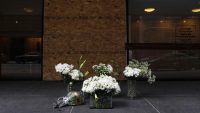 Flowers sit in front of a broken window of the Chicago Loop Synagogue, after someone broke a window and left images of swastikas, Saturday Feb. 4, 2017. (Abel Uribe / Chicago Tribune)